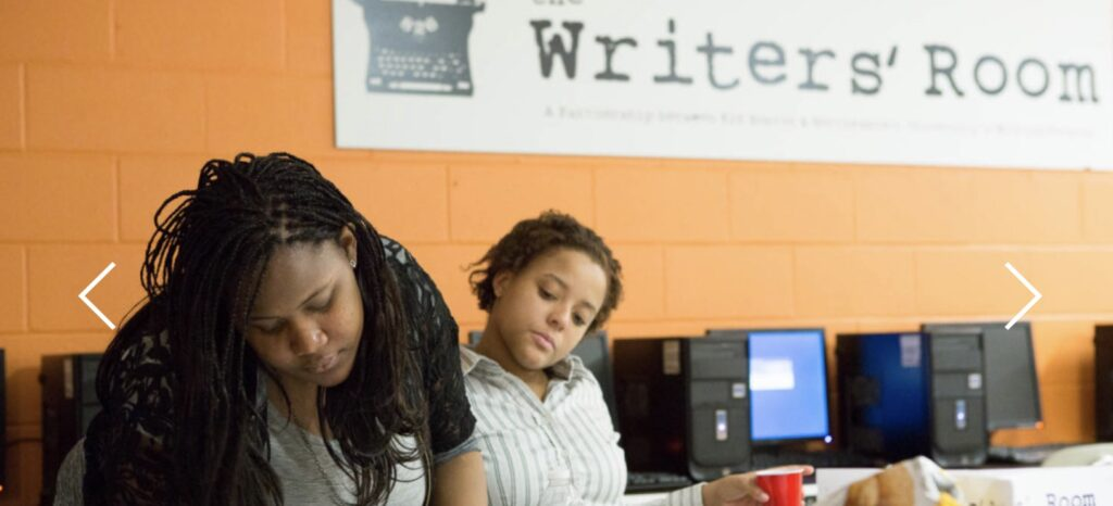 A mentor and a mentee in the writing center, the mentee looks on to the mentor writing