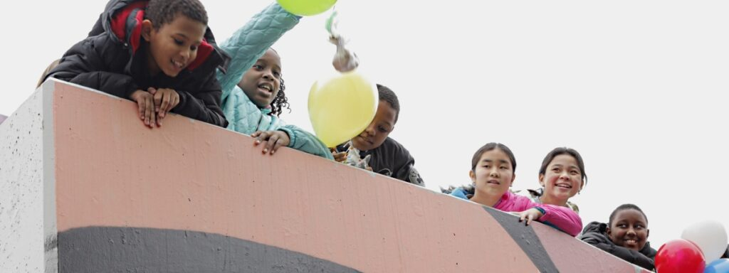 Group of kids dropping a balloon from a high building.