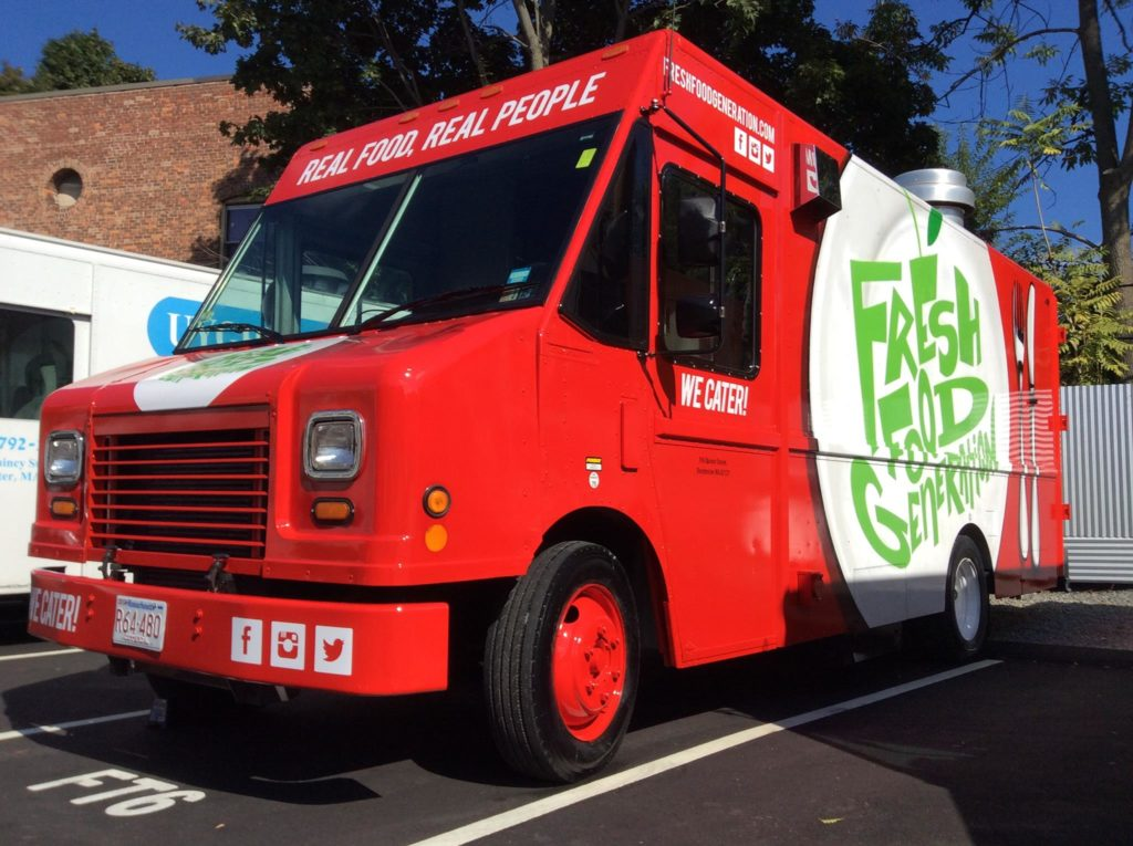 """An red food truck with the a sign that says """"Fresh food generations!"""""""